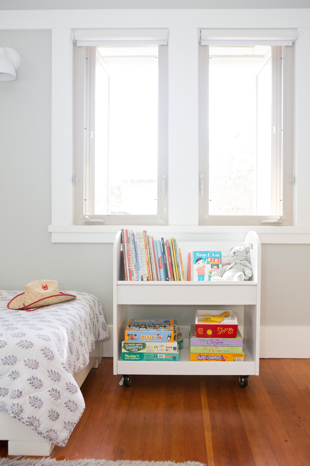 Kids room with book and game cart and West Elm quilt